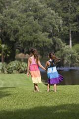 Hispanic girls walking in park holding hands