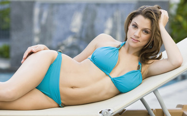 Caucasian woman in bikini laying on lounge chair
