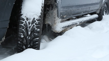 Snowtire on SUV during snowstorm.