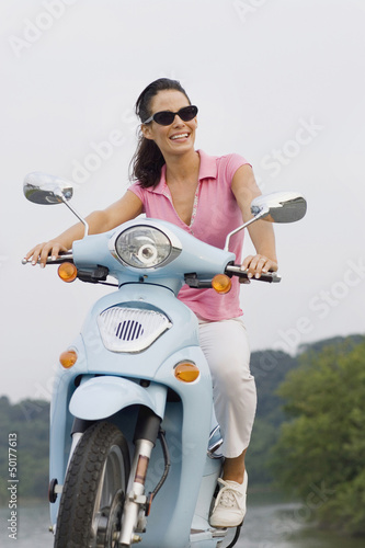 Smiling woman riding on scooter