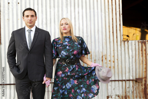 Caucasian couple in elegant clothes standing near wall