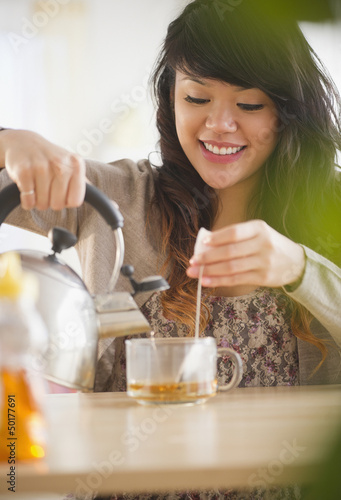 Pacific Islander woman making hot tea