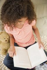 Mixed race girl reading book