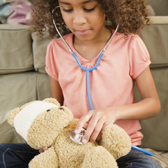 Mixed race girl using stethoscope on teddy bear