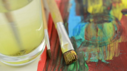 brush with yellow water color is cleaned in water glass.