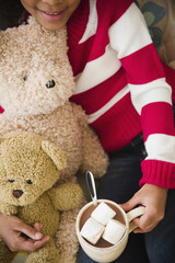 Mixed race girl with teddy bears drinking hot chocolate
