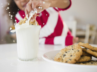 Mixed race girl dunking cookie into milk