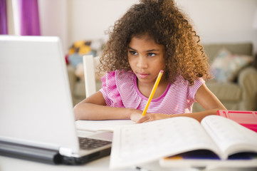 Mixed race girl doing homework with laptop
