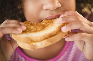 Mixed race girl eating sandwich