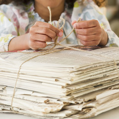 Mixed race girl tying bundle of newspapers