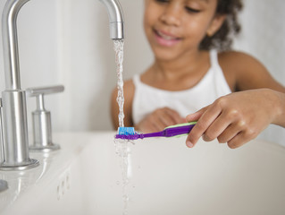 Mixed race girl brushing her teeth