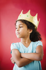 Mixed race girl with arms crossed wearing crown