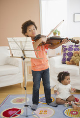 Black boy practicing violin in living room