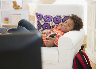 Black boy laying in chair watching television