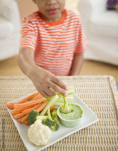 Black boy eating vegetables and dip