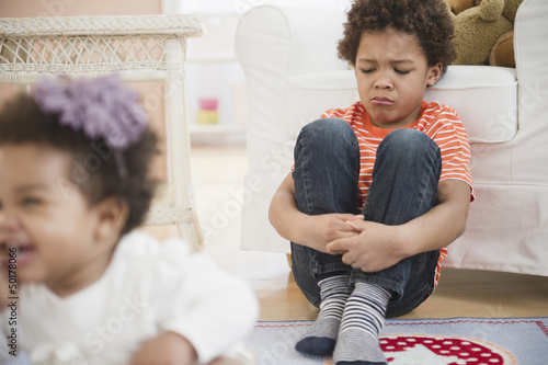 Sad Black boy sitting in living room