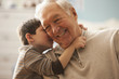 Caucasian boy telling grandfather a secret