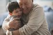 Caucasian man hugging grandson
