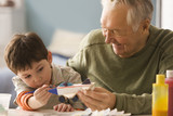 Caucasian man helping grandson paint toy airplane