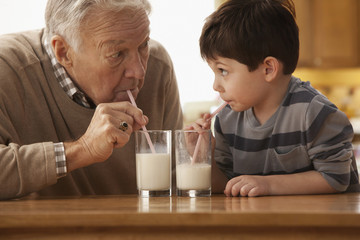 Caucasian grandfather and grandson drinking milk together