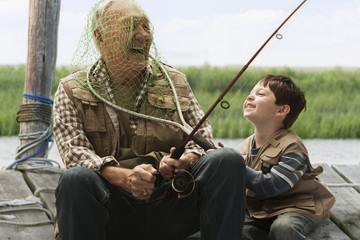 Caucasian boy putting fishing net over grandfather's head