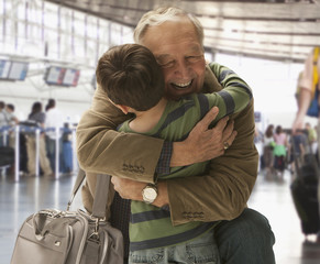 Caucasian man hugging grandson in airport