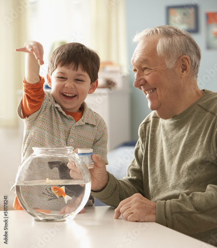 Caucasian man helping grandson feed goldfish