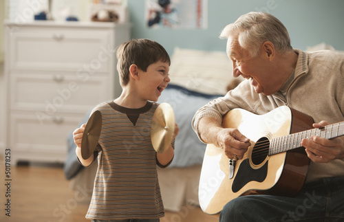 Caucasian man and grandson playing musical instruments together