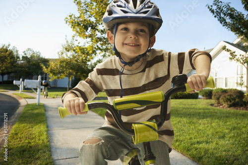 Caucasian boy riding bicycle on sidewalk