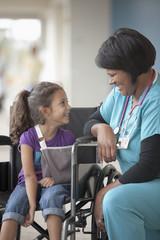 Nurse talking to girl in wheelchair