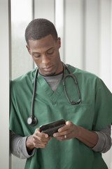 Mixed race doctor text messaging on cell phone