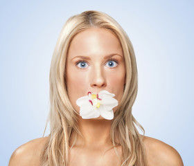 Caucasian woman with flower in her mouth