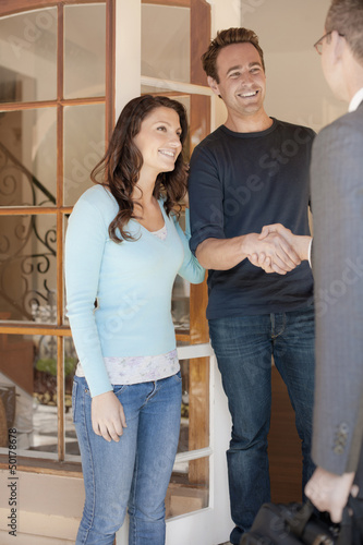 Hispanic couple greeting financial advisor