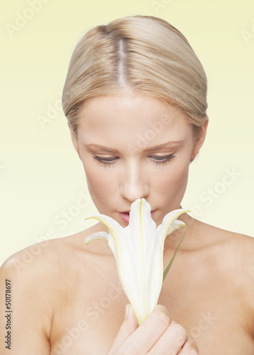 Caucasian woman smelling flower