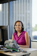 African American businesswoman working at desk in headset