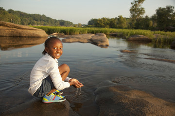 African American girl scooping water from river