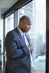 Serious African American businessman standing in office