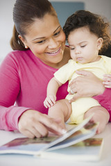 Mixed race mother reading book to baby
