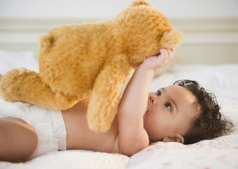 Mixed race baby holding teddy bear