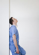 Caucasian surgeon leaning against wall