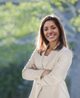 Smiling mixed race businesswoman with arms crossed