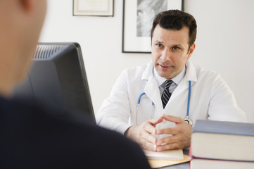 Mixed race doctor talking to patient