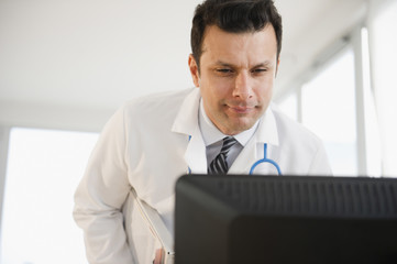 Mixed race doctor looking at computer monitor