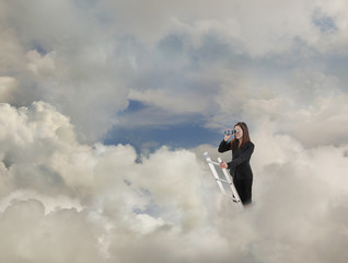 Mixed race businesswoman standing on clouds on ladder using binoculars