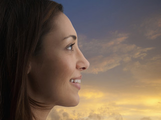 Smiling mixed race woman with sky in background