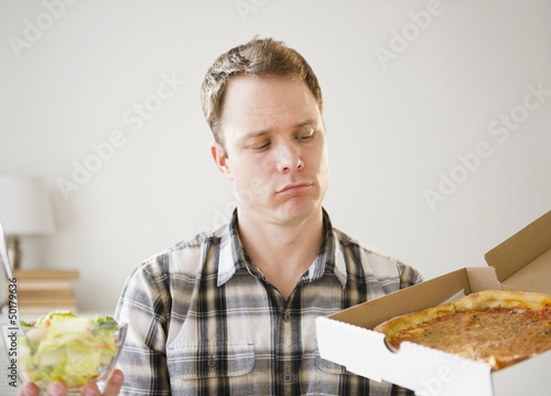 Caucasian man looking at pizza in box