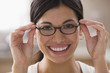 Mixed race woman putting on eyeglasses
