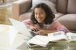 Hispanic girl doing homework on laptop