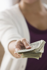 Mixed race woman holding out dollar bills
