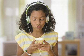 Hispanic girl listening to music on headphones